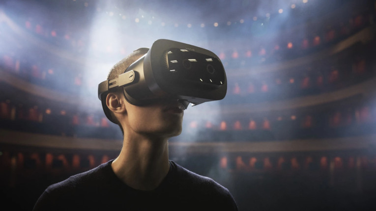 A man wearing virtual-reality goggles on a stage.